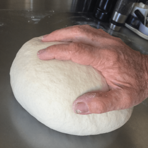 hand resting on ball of dough