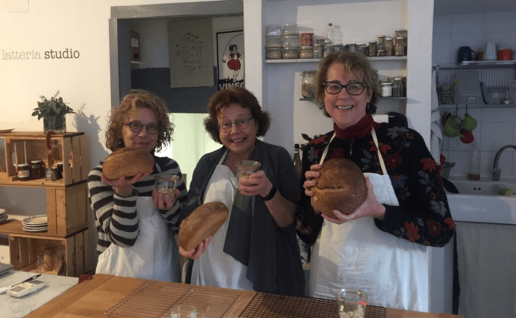 three happy bakers with their bread and sourdough starters