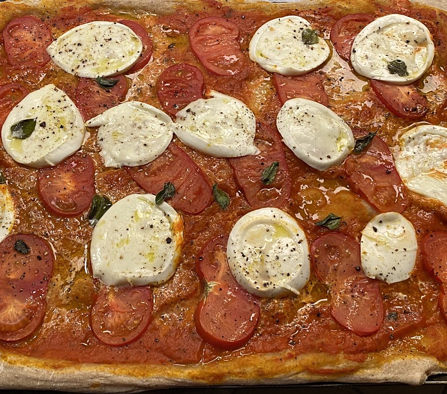 Pizza with mozzarella and fresh tomato on a tomato sauce base