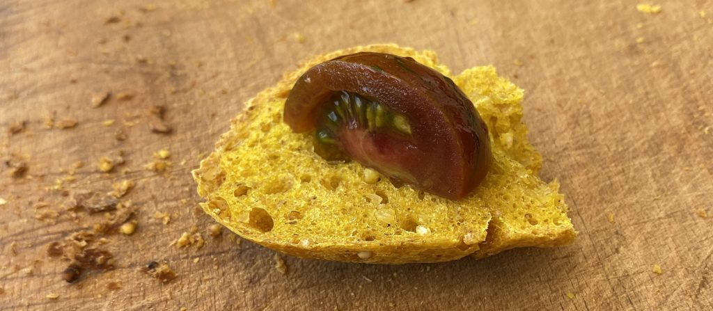 Dark tomato on a slice of golden turmeric bread